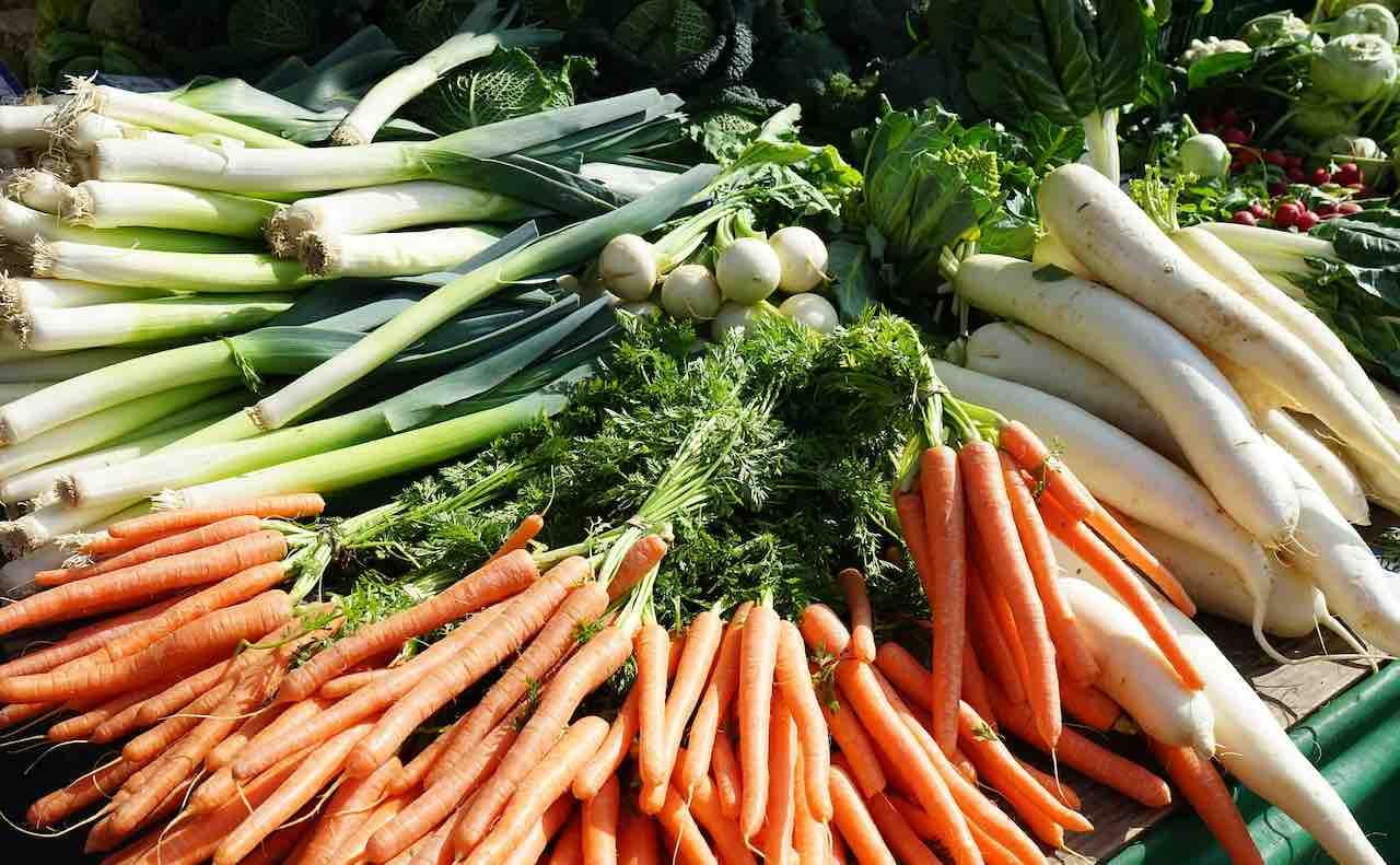 市場に並ぶネギとその他の野菜